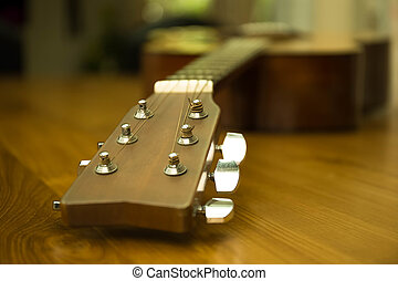 Headstock of acoustic guitar on wooden table