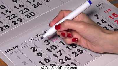 Female hand undercore 9 calendar day with blue marker and...