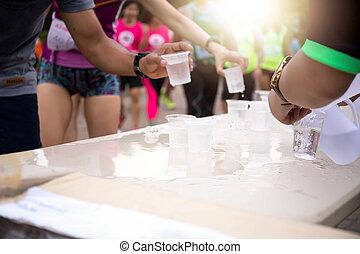 Volunteer people pouring water for athletes marathon runner
