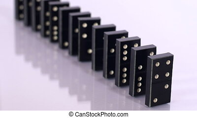 Falling black dominoes in slow motion - A straight line of...