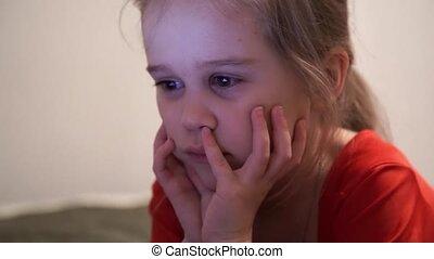 Little girl at night watching cartoons. - Little girl...