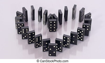 Dominoes in shape of heart falling - A finger pushes black...