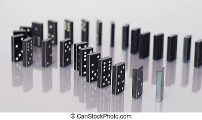 Falling row of dominoes - Curved line of dominoes falling in...