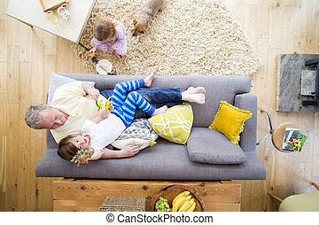 Having Fun at Grandad's House - Senior man is lying on the...