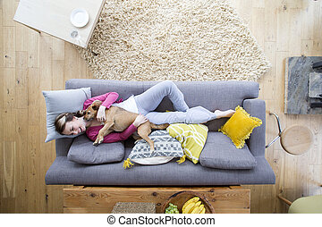 Don't Lick My Face! - Young woman is lying on the sofa in...