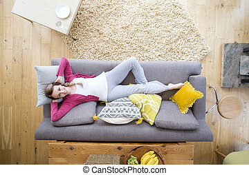 Woman Relaxing on Sofa - Beautiful woman is lying on the...