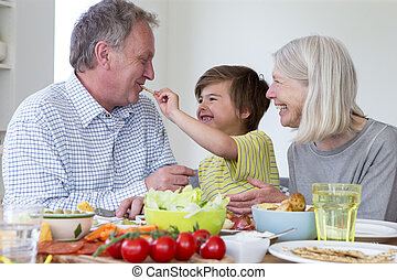 Feeding Grandad a Cream Cracker - Little boy is feeding his...