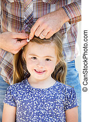 Dad Doing Daughter's Hair - Little girl is smiling for the...