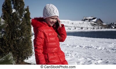 Little girl in a red jacket talking on the phone