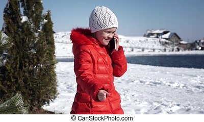 Little girl in a red jacket talking on the phone - A little...