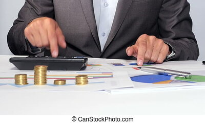 Businessman calculating money - BUsinessman sitting at his...