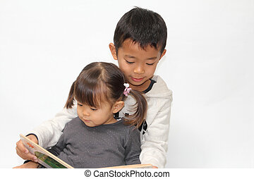 Japanese brother and sister reading a picture book (7 years...