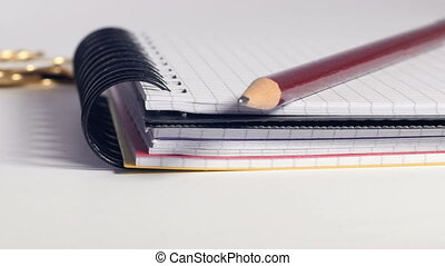 Pencil, notebook, coins and calculator on table - Wooden...