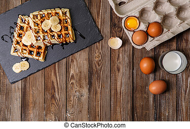 Homemade waffles on wooden table - Homemade waffles, eggs in...