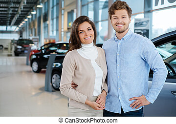 Beautiful young couple looking a new car at the dealership...