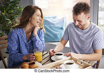 Couple having some laughs at dining table