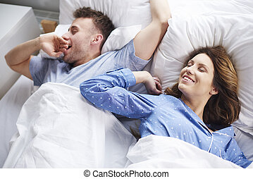 Couple stretching and yawning in bed