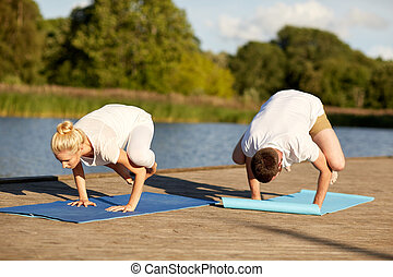 couple making yoga crow pose outdoors - fitness, sport,...