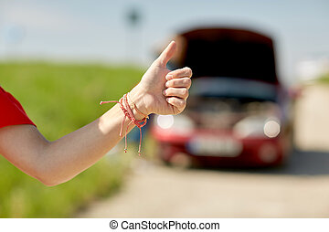 woman with broken car hitching at countryside - road trip,...