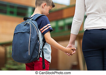 elementary student boy with mother at school yard -...