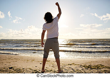 man with rised fist on beach - people, success, achievement...