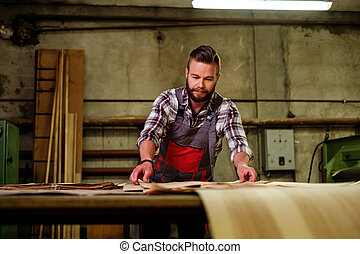 Carpenter doing his job in carpentry workshop