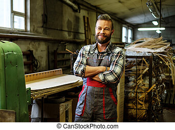 Carpenter on his workplace in carpentry workshop