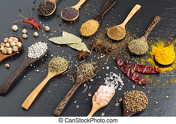 Variety of herbs and spicies ingredients. peppercorn, mustard, oregano, turmeric, paprika, pepper, anise, coriander, rosemary, salt, thyme, bay leaf on black stone background.