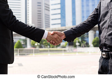 Business agreement hand shaking in front of modern building...