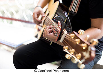 Man Practicing in playing acoustic guitar with a capo clip...
