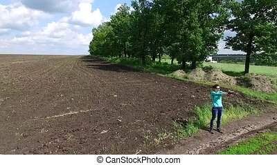 young girl practicing shooting in countryside on field,...