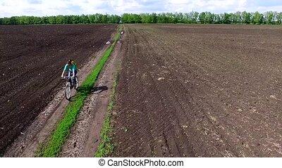 bycyclist riding bike in a field - gil bycyclist riding bike...