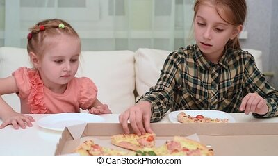 little girl giving a piece of pizza to her younger sister, video