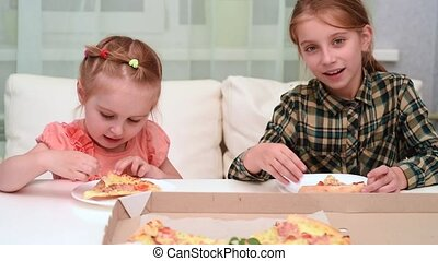 little girl eating pizza and her older sister waving her hand