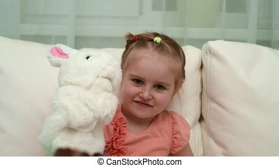 happy little girl playing her toy at birthday table - happy...