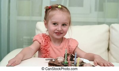 pretty little girl getting white hare toy at her birthday table