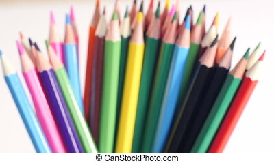 Forming a stack of colorful pencils - Hand adds bunch of...