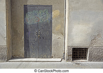 Front of abandoned house with grey door.