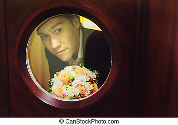 Man with a bouquet looks through the round window