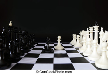 Beginning of chess game. Chess pieces against black background