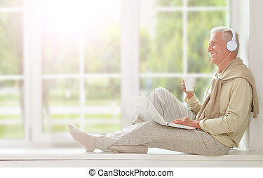 mature man sitting on window sit using laptop, listening to...