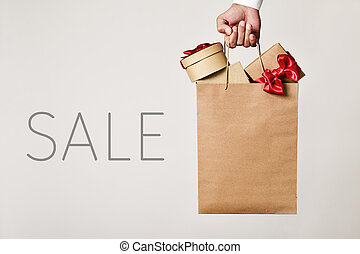 shopping bag with gifts and word sale - closeup of the hand...
