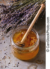 Honey and lavande - Open glass jar of liquid honey with...