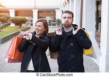 Man very bored of the shopping addiction of his girlfriend
