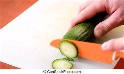Chopping the cucumber - Chopping the fresh cucumber into...