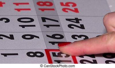 Business woman finger pushing red marker on calendar page....