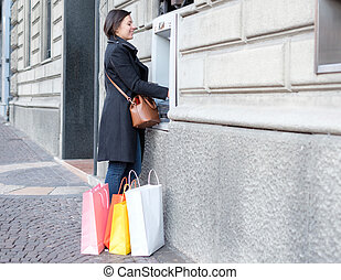 Woman making a bank withdrawal in an atm cash machine