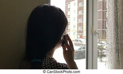 girl talking on a cell phone near a window - A young girl...