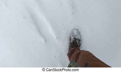 foot man walking in the snow. POV video