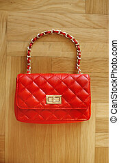 Fashion women leather red handbag isolated on wooden parquet...